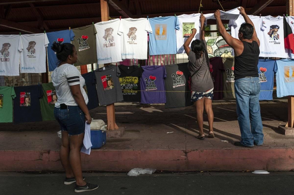 Partidarios progubernamentales miran camisetas que promueven al presidente nicaragüense Daniel Ortega y al partido gobernante Frente Sandinista de Liberación Nacional, antes de una manifestación en conmemoración del levantamiento que derrocó a la familia Somoza en Managua, Nicaragua, el jueves 19 de julio de 2018. (AP Foto / Cristobal Venegas)