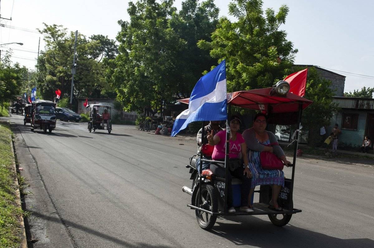 Moto-taxis decorados con banderas del Frente Sandinista de Liberación Nacional y banderas nacionales nicaragüenses participan en una caravana antes de una manifestación conmemorativa del levantamiento que derrocó a la familia Somoza en Managua, Nicaragua, el jueves 19 de julio de 2018. (AP Foto / Cristobal Venegas)