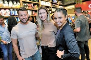 O personal trainer com as digitais influencers Aline Mareto e Emily Finamore na badalada reinauguração da Fast Nutri, em Vila Velha