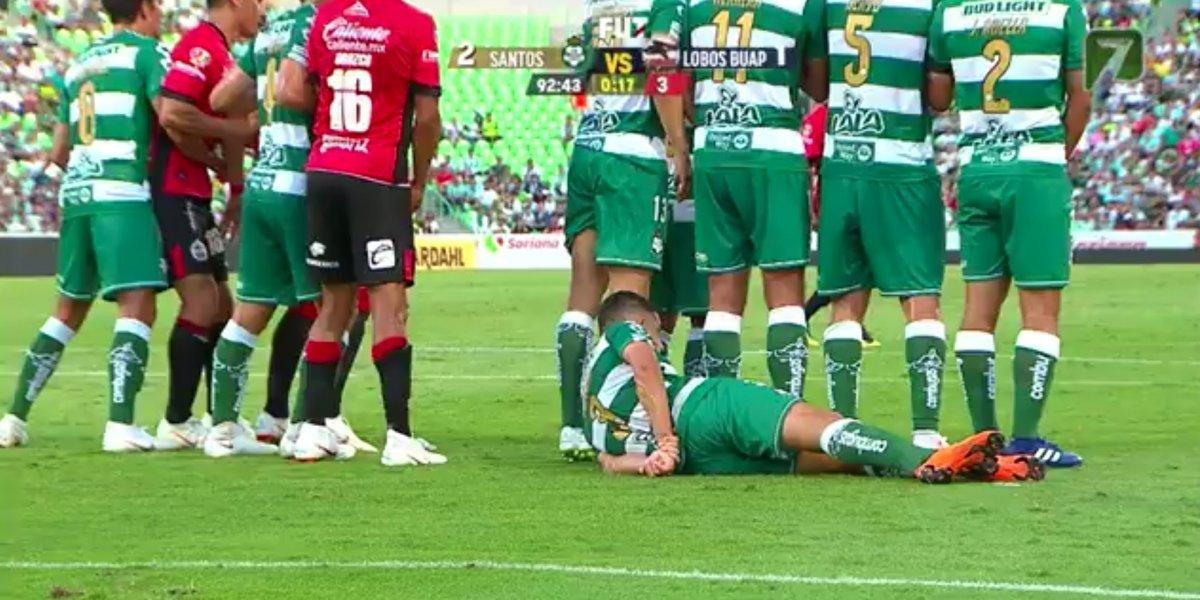 Gerardo Alcoba se tiende en el pasto detrás de la barrera para evitar que pase el balón