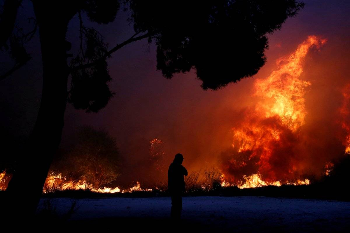 Homem olha para as chamas do incêndio florestal queimando cidade de Rafina, ao leste de Atenas, na Grécia Costas Baltas/Reuters
