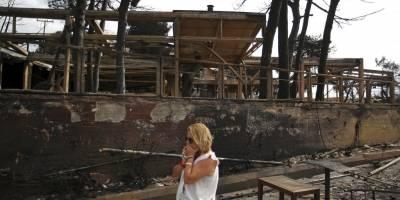 Una mujer camina entre los restos calcinados de las propiedades quemadas en Mati, al este de Atenas, el martes 24 de julio de 2018. (Foto AP / Thanassis Stavrakis)