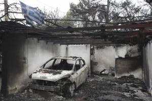 Una bandera de Grecia ondea sobre los restos calcinados de un auto y una casa en Mati, al este de Atenas, el 24 de julio de 2018. (AP Foto/Thanassis Stavrakis)
