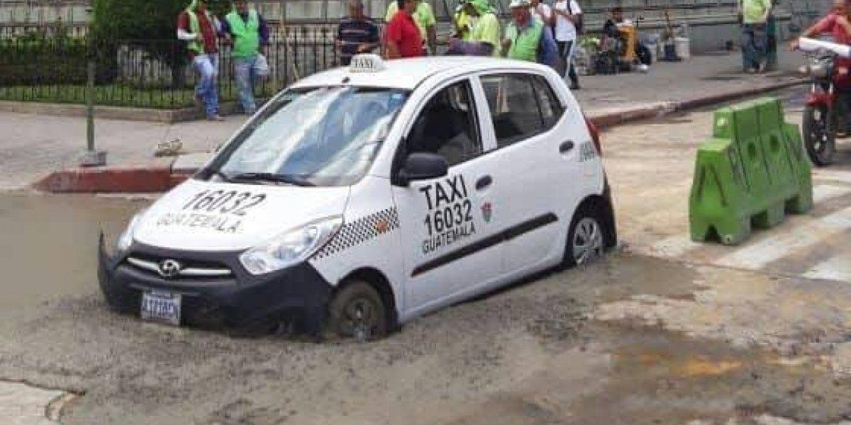 Taxista no respeta señalización y queda entre el cemento fresco