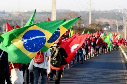 La expresidenta Dilma Rousseff muestra a los seguidores del PT la inscripción de Lula como candidato. AFP