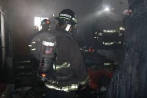 Los socorritas ingresan a la bodega para controlar el incendio.