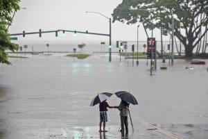 Personas se paran cerca de las inundaciones provocadaspor las lluvias del huracán Lane, haciendo que la intersección de la avenida Kamehameha y la calle Pauahi sea intransitable. / AP