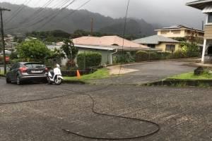 Una línea de servicio público tendida en la calle en el barrio Nuuanu de Honolulu, el viernes 24 de agosto de 2018, una muestra de los vientos del huracán Lane. / AP