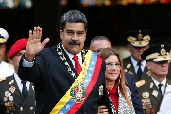 En esta fotografía de archivo del 24 de mayo de 2018, el presidente de Venezuela, Nicolás Maduro, y su esposa, Cilia Flores, saludan a su llegada a un desfile militar en el Fuerte Tiuna en Caracas.