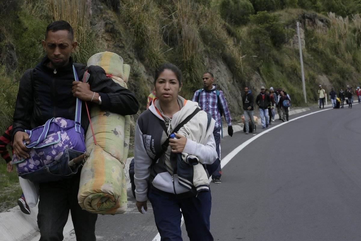 Migrantes venezolanos que no tienen con pasaporte caminan por la carretera Panamericana después de cruzar el puente internacional Rumichaca de Colombia, antes de llegar a un punto de inspección migratoria en Rumichaca,