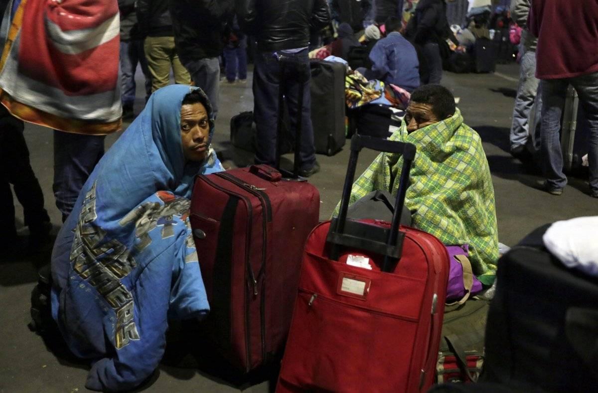 Un grupo de migrantes venezolanos espera una decisión de las autoridades de migración que les permita entrar a Ecuador sin pasaporte después de que nuevas regulaciones exigieran el documento en el país en Rumichaca