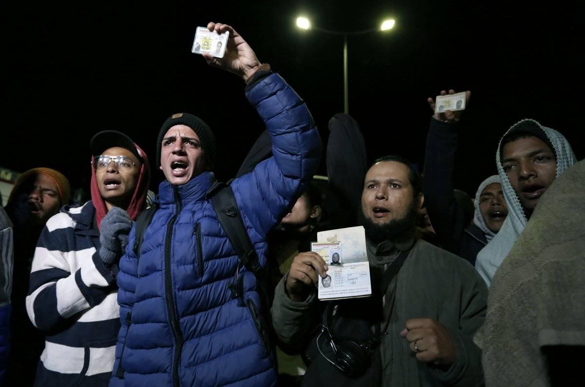 Un grupo de migrantes venezolanos espera una decisión de las autoridades de migración que les permita entrar a Ecuador sin pasaporte después de que nuevas regulaciones exigieran el documento en el país en Rumichaca, AP