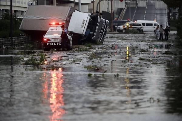 Un policía se encuentra junto a una carretera inundada tras un poderoso tifón en Osaka, en el oeste de Japón, el 4 de septiembre de 2018. (Kota Endo / Kyodo News vía AP)