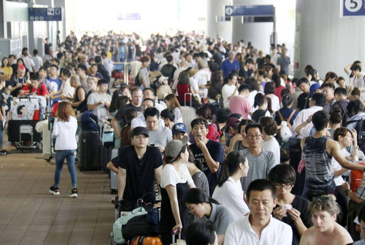 Los pasajeros varados hacen fila para esperar autobuses especiales en el Aeropuerto Internacional de Kansai después del poderoso tifón en Osaka, al oeste de Japón, el miércoles 5 de septiembre de 2018. (Noticias de Kyodo vía AP)