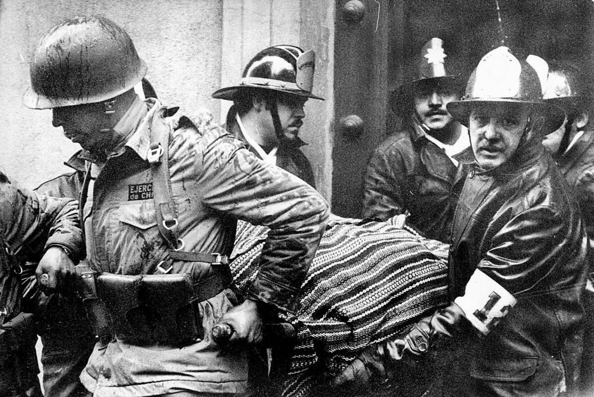 Soldados y bomberos portan el cuerpo del presidente Salvador Allende, envuelto en un poncho boliviano, del destruido palacio presidencial La Moneda después del golpe del 11 de septiembre de 1973 encabezado por el general Augusto Pinochet que puso fin al g