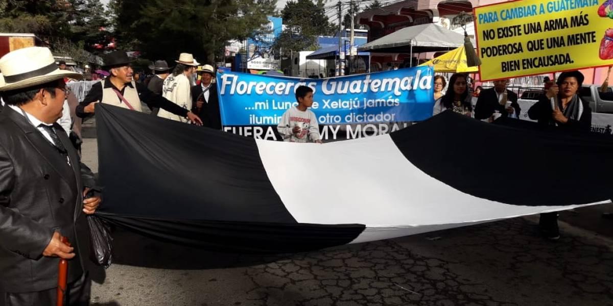Autoridades ancestrales portan bandera negra en desfile en Quetzaltenango