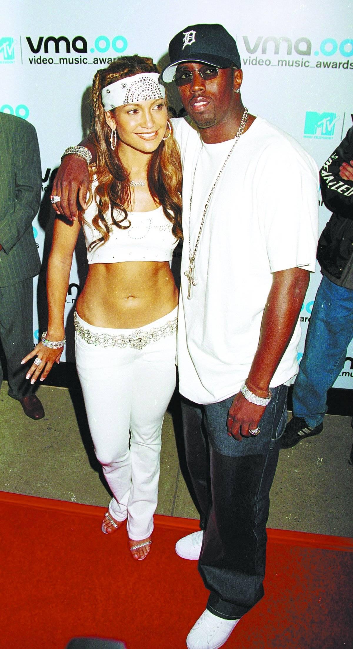 """O estilo """"JLo"""". Cós baixo ou calças jeans brancas, tops tomara que caia e botas de cano branco... Jennifer Lopez tinha um estilo """"hip-hop"""" notável no começo do século, e seu look não ficou para trás. Ao mesmo tempo, diversas estrelas passaram a adotar os tops da diva e eles ficaram populares entre usuários do Instagram e, logo, nas lojas.   Reprodução"""