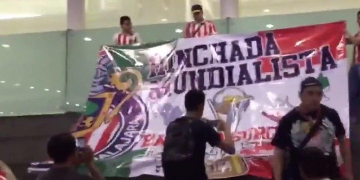 Aficionados reciben a Chivas con gran fiesta en el AICM