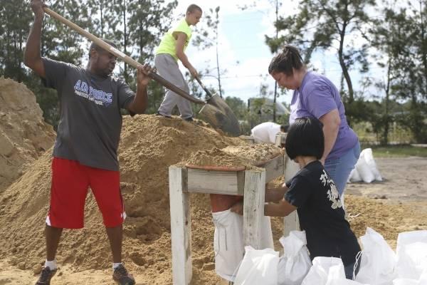 Haskel Johnson, Daniel Tippett, Jennifer Tippett y Nobuko Johnson llenan sacos de arena en Lynn Haven, Florida, el lunes 8 de octubre de 2018, previo a que el huracán Michael toque tierra en el estado. (Patti Blake /News Herald via AP)