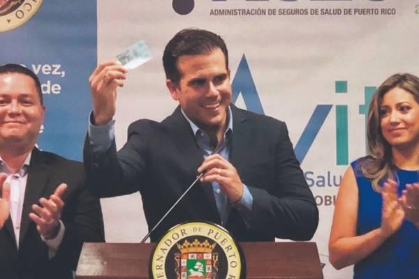 El gobernador muestra una tarjeta del nuevo modelo de salud Vital. David Cordero