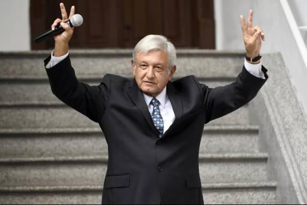 Andrés Manuel López Obrador levantando los brazos
