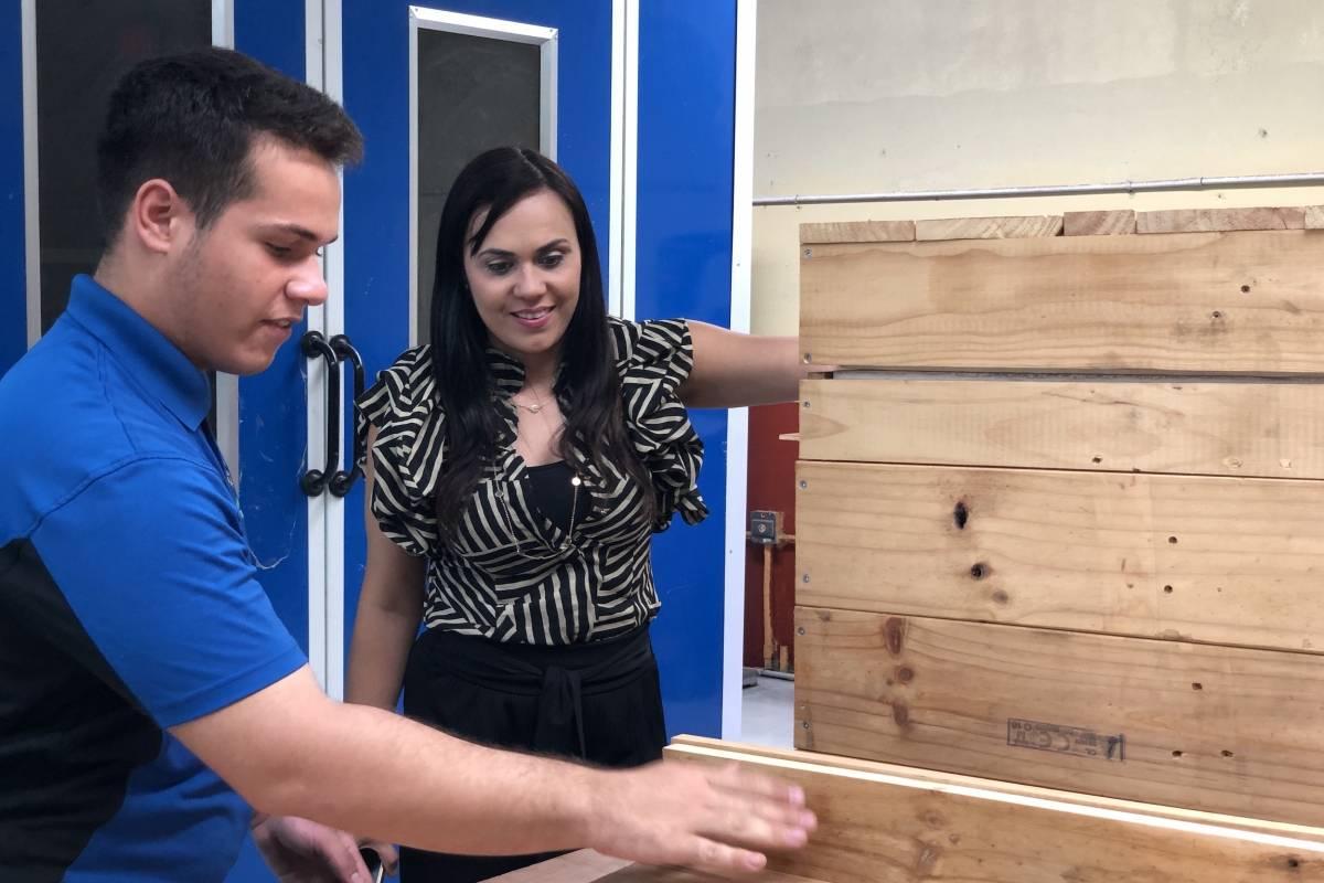 El estudiante Samuel Dodd le muestra el taller a Ivelisse Torres Rivera, comisionada de la Comisión de Desarrollo Cooperativo de Puerto Rico (CDCoop)./ Foto: David Cordero Mercado