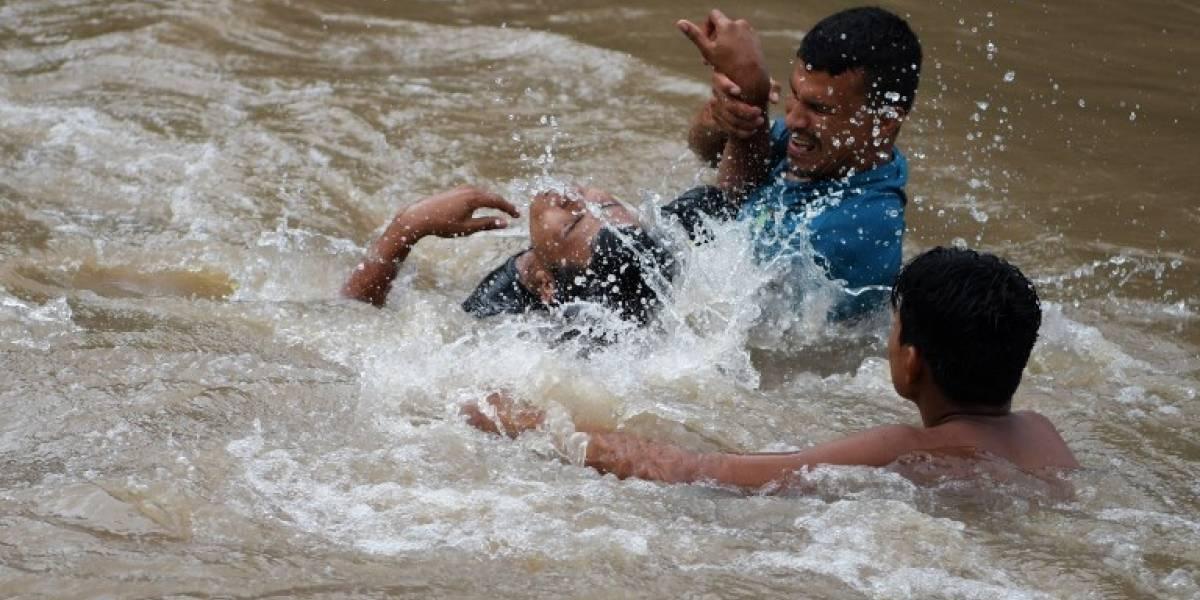FOTOS. Hondureños desafían río para ingresar a El Salvador y alcanzar caravana migrante