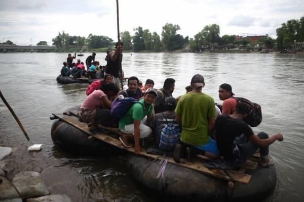 Migrantes hondureños de segunda caravana cruzan río entre Guatemala y México