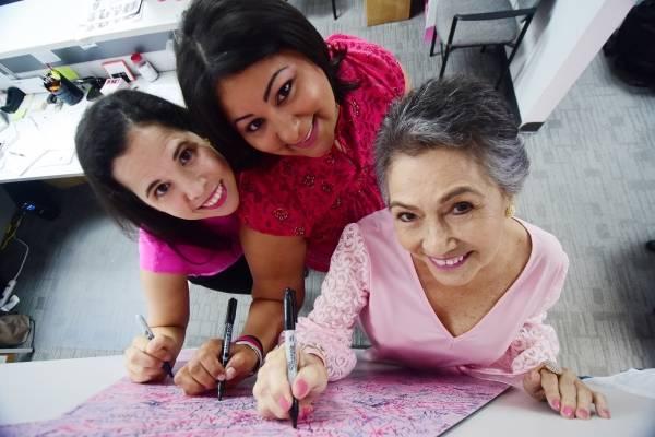 Marla, Judith y Gloria plasman su firma en el lazo rosado de la Fundación Susan G. Komen Puerto Rico. Foto: Dennis Jones