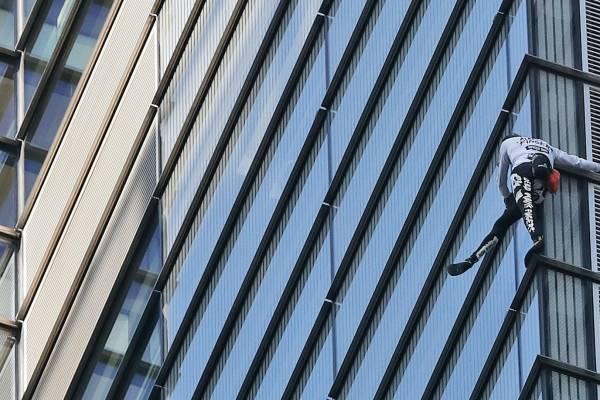 Personas observan desde el interior de la torre Heron que sube el alpinista urbano francés, Alain Robert, en Londres, el jueves 25 de octubre de 2018.
