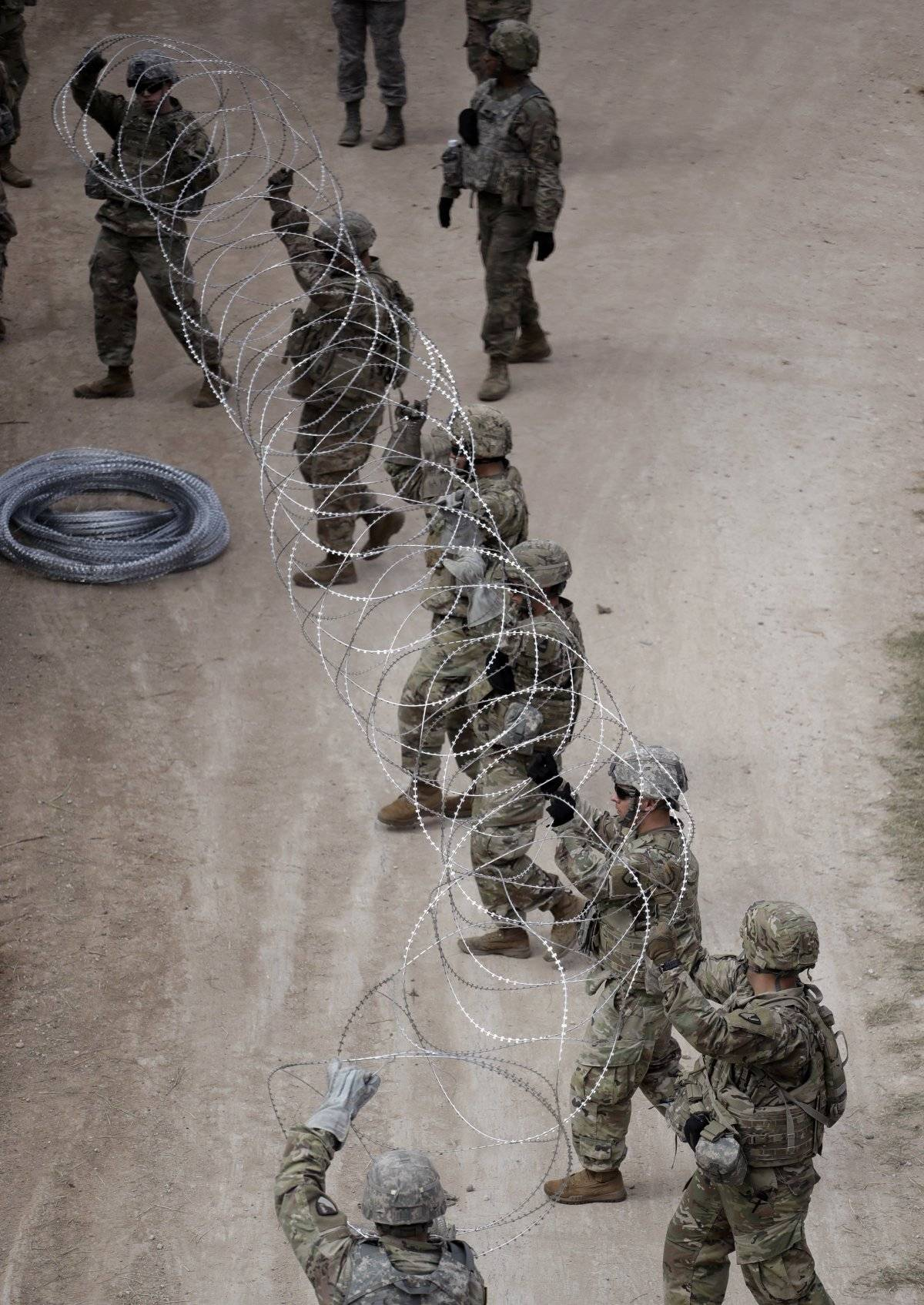 Miembros del ejército de Estados Unidos colocan alambradas a lo largo de la frontera de EU