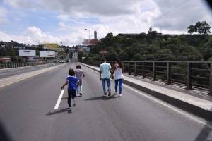 Personas caminan por el puente Belice