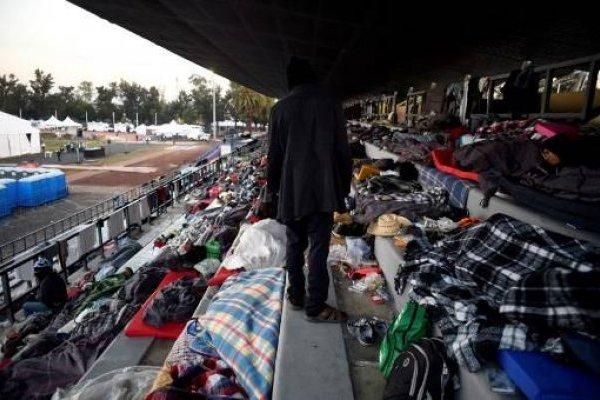 Migrantes hondureños descansan en un estadio en Ciudad de Méxicoq
