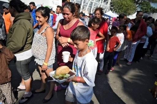 Familias migrantes hondureñas se alimentan en ciudad de México.