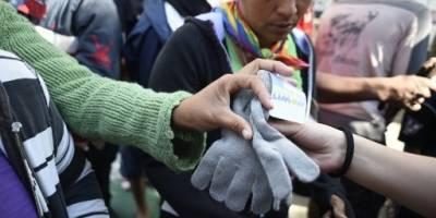 Migrantes hondureños reciben guantes donados para soportar el frío en ciudad de México.