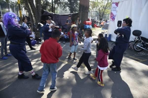 Una payasita entretiene a niños que son parte de la caravana migrante.
