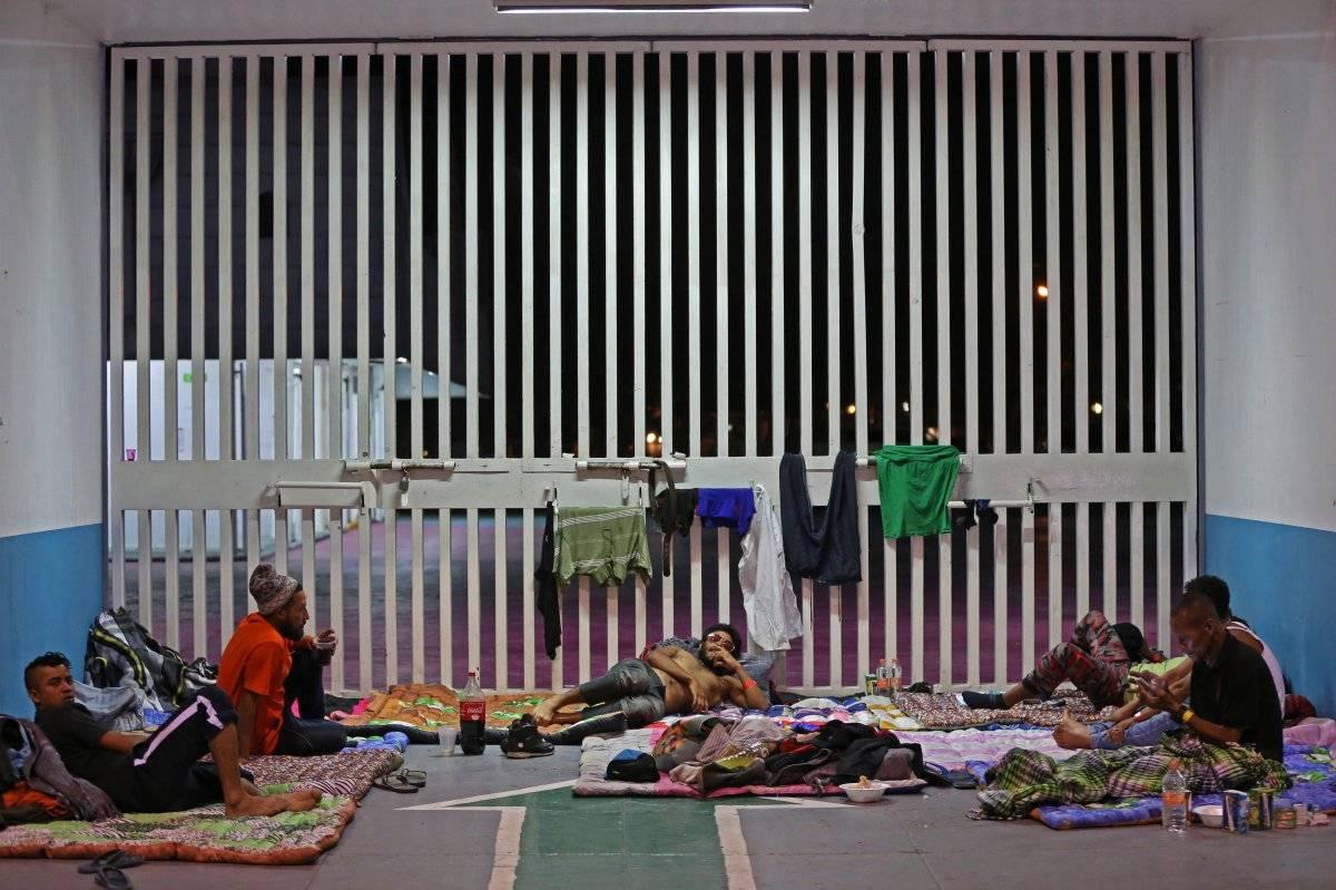 Decenas de migrantes escalan la valla fronteriza cerca de Tijuana