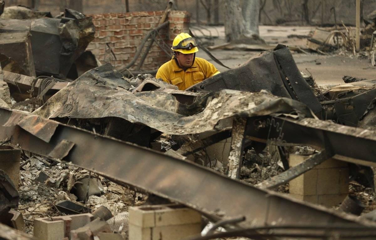 Un bombero mira a través de una casa destruida por el Camp Fire donde se encontraron restos humanos, el domingo 11 de noviembre de 2018, en Paradise, California (Foto: AP / John Locher)
