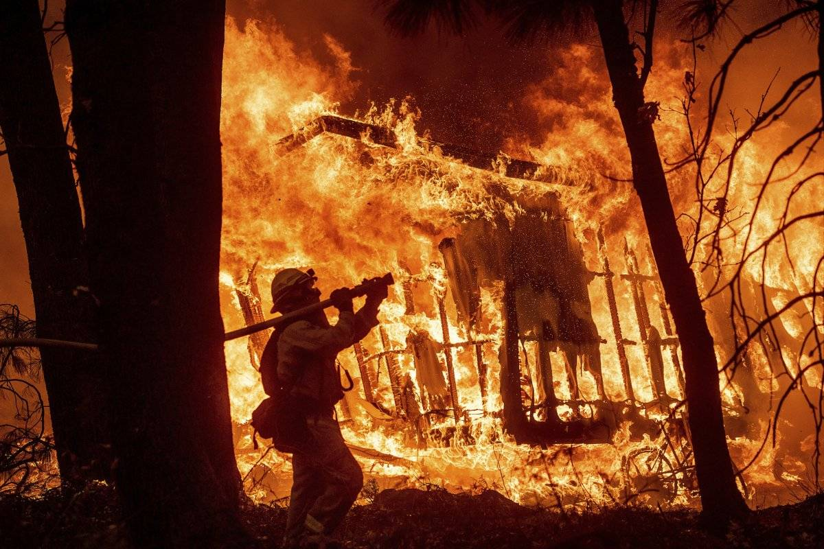 El bombero José Corona rocía agua mientras las llamas se consumen una casa en Magalia, California, el viernes 9 de noviembre de 2018. (Foto de AP / Noah Berger, archivo)