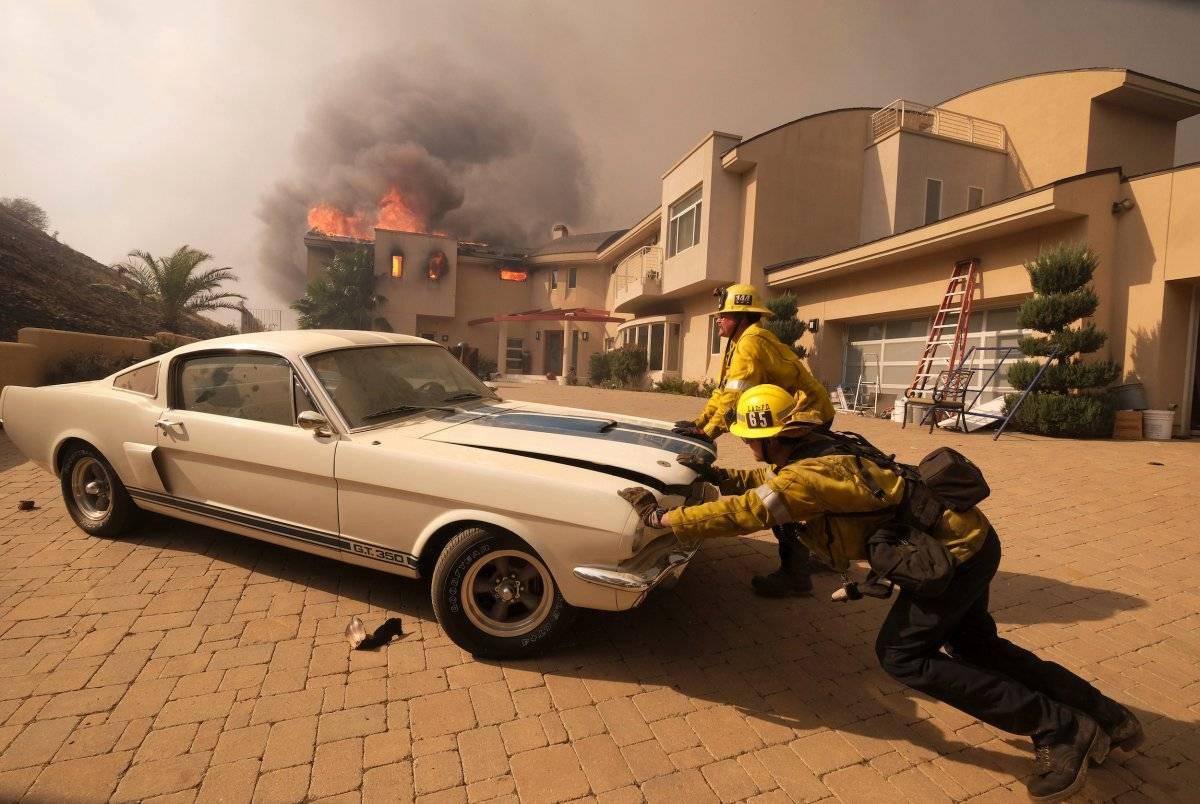 Los bomberos empujan un vehículo desde un garaje mientras un incendio forestal quema una casa en Malibu, California, el viernes 9 de noviembre de 2018. (Foto: AP / Ringo H.W. Chiu, archivo)