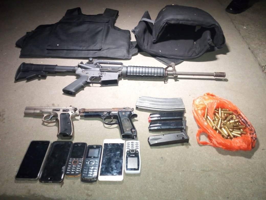 Armas de fuego, municiones, chalecos blindados y teléfonos incautados a presuntos pandilleros en Villa Nueva. Foto: PNC