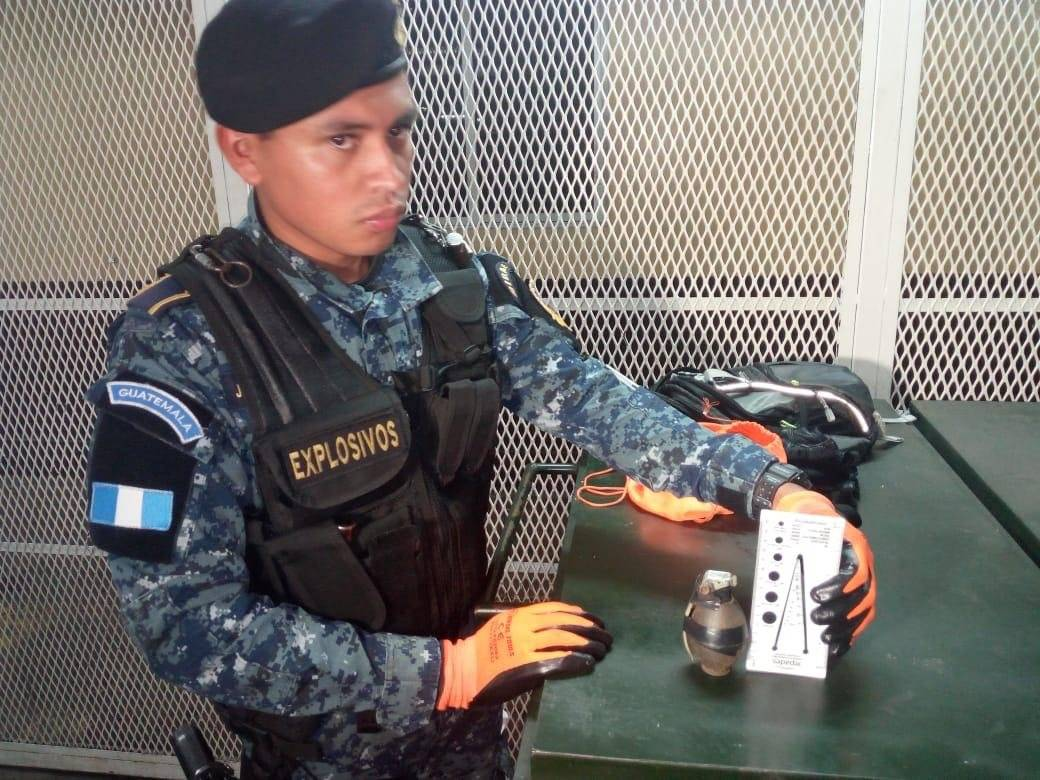 Un policía muestra la granada que pretendía lanzar el capturado. Foto: PNC