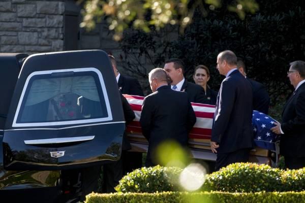 Portadores llevan el féretro del expresidente George H.W. Bush a la carroza funeral el lunes, 3 de diciembre del 2018. en Houston, Texas.