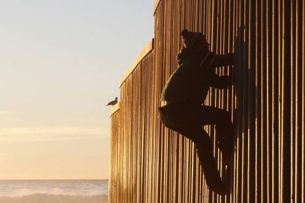 Migrantes en muro de EE. UU.