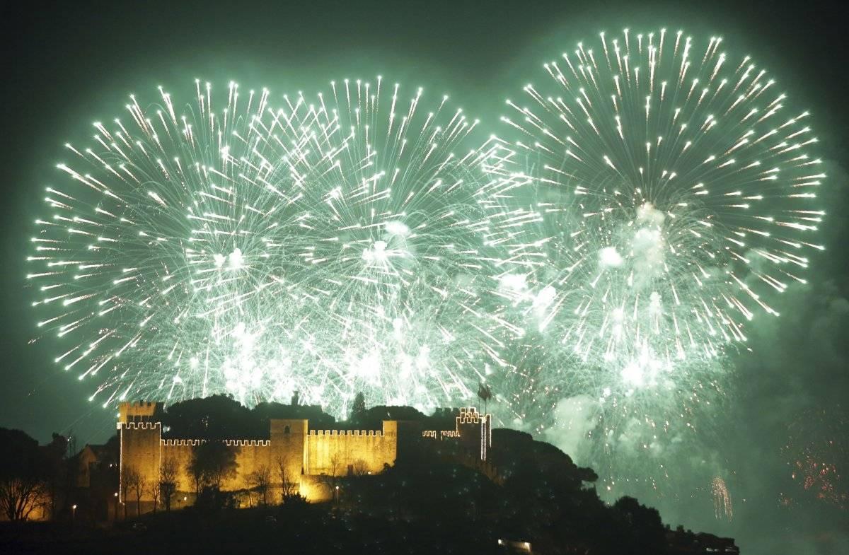 Foto: Fuegos artificiales iluminan el cielo por el Año Nuevo detrás del castillo de San Jorge en Lisboa, Portugal AP