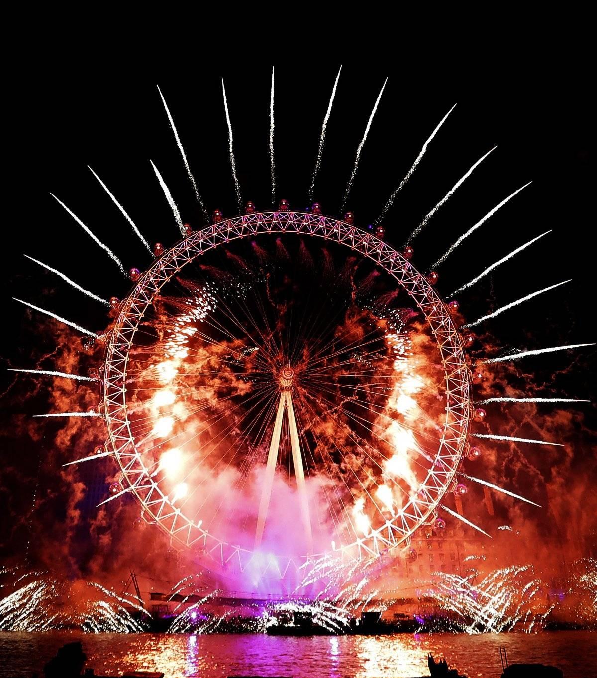 Foto: Fuegos artificiales iluminan la rueda de la fortuna de Londres por el Año Nuevo AP