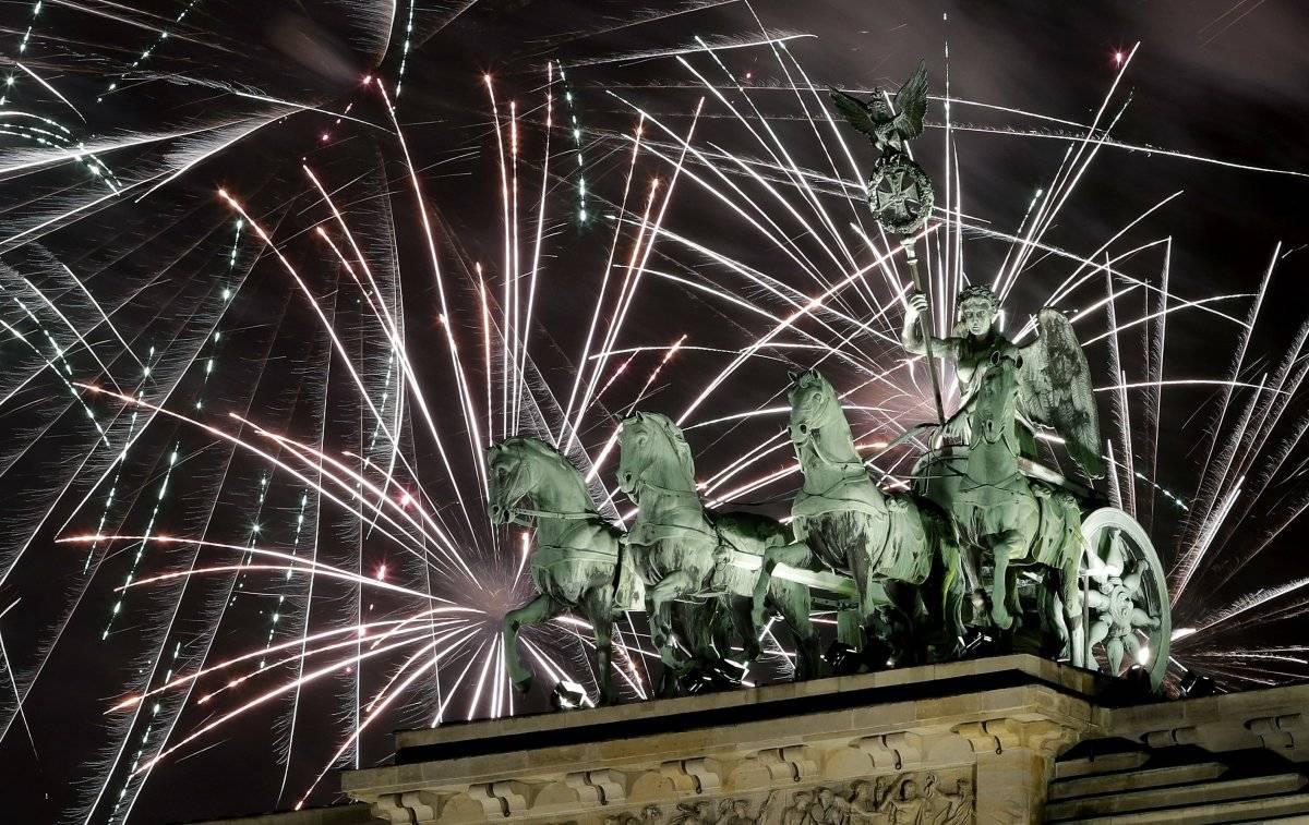 Foto: Fuegos artificiales iluminan el cielo encima de la Puerta de Brandenburgo por el Año Nuevo en Berlín, Alemania AP