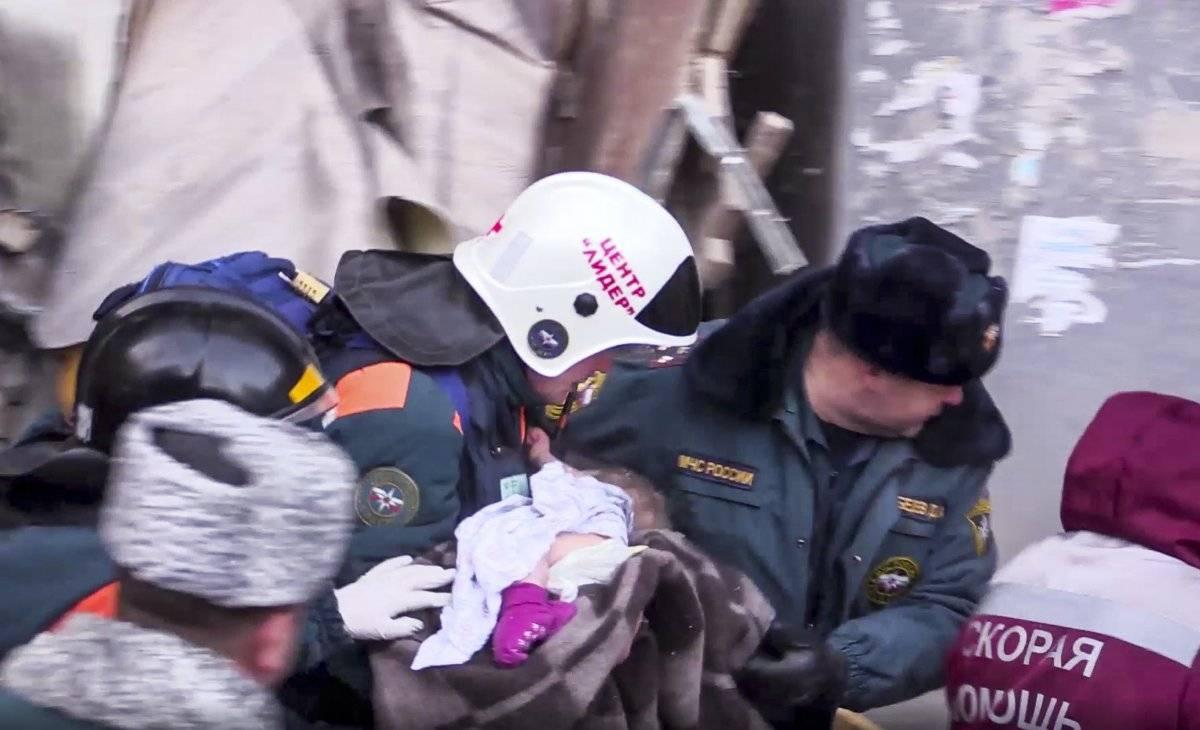 En esta fotografía del Ministerio de Manejo de Emergencia de Rusia, tomada de la televisión, se observa a empleados de la dependencia cuando llevan a un bebé de 10 meses de edad que fue rescatado entre los escombros de una sección derrumbada de un edificio de apartamentos en Magnitogorsk, Rusia, el martes 1 de enero de 2019.. Ministerio de Manejo de Emergencias de Rusia vía AP