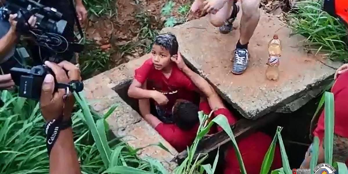 Criança cai em bueiro ao tentar salvar cachorro de enchente; veja momento do resgate