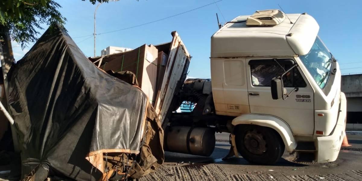 Caminhão tomba na avenida do Estado e derruba muro de casa